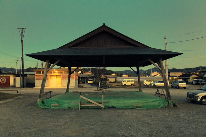 "PLACES OF JAPAN 08 - ""SUMO TENT RING"" I say it's a Sumo Tent, Vicki says it's a Sumo Pit, but then she changes her mind and says that it's actually a Sumo Ring. Since she's obviously not sure what the hell it is I decided to follow my gut and go with ""tent"". Obviously Vicki wasn't too happy with this decision and punched me in the gut, so I crossed out tent and wrote ""ring"". Everyone wins. Anyway, this tent was literally two blocks from Vicki's Grandmom's house, how cool is that? I like picturing Vicki's cute little 89-year-old Grandmom sneaking out at midnight and participating in an ""Underground Senior Sumo Club"". As awesome as Fight Club was, I think a similar film starring Vicki's Grandmom and my Grandpa Herb called Senior Sumo Club would be much funnier."