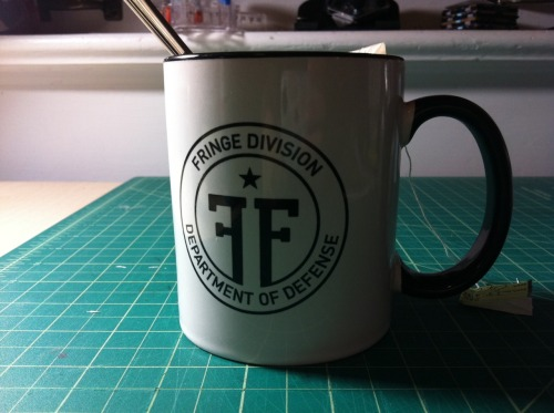 So hey: Fringe Mugs are finally in. And they look awesome. Anyone still interested? i'm working on getting a real sales post/photo shoot up but if you want one of the 36 mugs I have, it's first-come first-serve. Fringe Division Mug - USA ($20+$5 Shipping) Fringe Division Mug - International ($20+$10 Shipping)