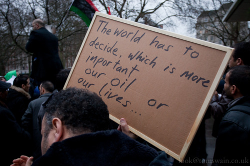 A man holds up a sign at a Lybian anti-Gaddafi protest outside the US Embassy in yesterday. London, UK.