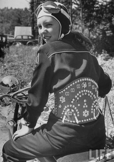 MotoLady in 1947.  Woman riding motorcycle and wearing decorated leather belt.
