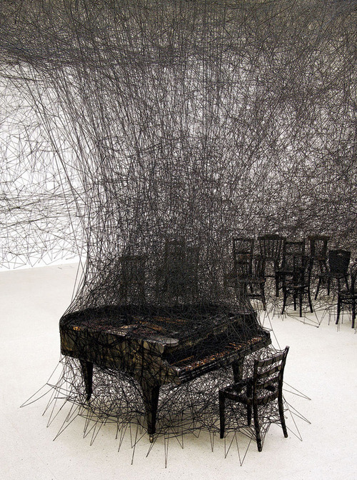 "stacccy:  anniekroy:   Chiharu Shiota, ""In Silence"" (2008).  Chiharu Shiota is a spider-woman – one who clambers around in the skeins of our unconscious. In her best-known installations she weaves black yarn into hectic webs that take over entire galleries and in which personal objects are found cocooned. Sound of silence: When Shiota was nine years old her neighbour's house burned down; the following day the artist saw a charred piano amongst the ruins. This instrument that lost its sound has haunted the artist and inspired various works in which she sets alight to a grand piano, then displays the remains within an installation of black thread. READ MORE.  incredible"
