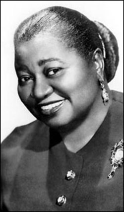 "Hattie McDaniel Arrives at the Coconut Grove by Rita Dove late, in aqua and ermine, gardeniasscaling her left sleeve in a spasm of scent,her gloves white, her smile chastened, purse giddywith stars and rhinestones clipped to her brilliantined hair, on her free arm that fine Negro,Mr. Wonderful Smith.It's the day that isn't, February 29th,at the end of the shortest month of the year—and the shittiest, too, everywhereexcept Hollywood, Californiawhere the maid can wear mink and still be a maid,bobbing her bandaged head and cursingthe white folks under her breath as she smiles and shoos their silly daughtersin from the night dew…what can she bethinking of, striding into the ballroomwhere no black face has ever showed itselfexcept above a serving tray?Hi-Hat Hattie, Mama Mac, Her Haughtiness,The ""little lady"" from Showboat whose nameBing forgot, Beulah & Bertha & Malena& Carrie & Violet & Cynthia & Fidelia,one half of the dark Barrymores—dear Mammy, we can't help but hug you crawl intoyour generous lap tease youwith such arch innuendo so we can feel thatmuch more wicked and youthful and sleek but oh whatwe forgot:  the four husbands, the phantompregnancy, your famous parties, your celebratedice box cake.  Your giggle above the red petticoat's rustle,black girl and white girl walking hand in hand down the railroad tracksin Kansas city, six years old.The man who advised you, nowthat you were famous to 'begin eliminating""your more common acquaintancesand your reply (catching him square in the eye):  ""That's a good idea.I'll start right now by eliminating you.""Is she or isn't she?  Three million dishes,a truckload of aprons and headrags later, and hereyou are:  poised, between husbandsand factions, no corset wide enoughto hold you in, your huge face a dark moon splitby that spontaneous smile – your trademark,your curse.  Not matter, Hattie:  It's a long, beautiful walkinto that flower-smothered standing ovation,so go onand make them wait.  Rita Dove"