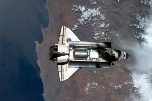 fuckyeahspace:  The International Space Station casts a shadow on the Space Shuttle Discovery.
