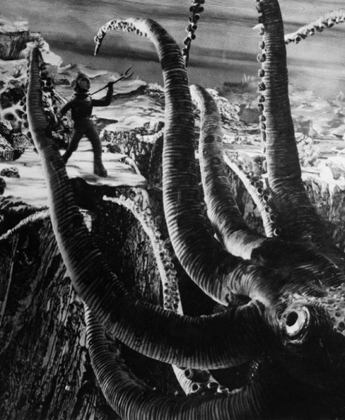"via The Fabulous World of Jules Verne (1958, dir. Karel Zeman), an adventure film based on 20,000 Leagues Under the Sea, Mysterious Island and other Verne tales: ""This is a live-action black and white movie — but it uses every camera trick and every form of animation known in 1958…Methods include stop-motion, paper cutout, drawing and painting animation, drawn foregrounds and backdrops, dissolves, miniatures and models, double exposure (probably in-camera and superimposition), still images, traveling and stationary mattes — they're all here. There were at least eight people watching; someone yelled out at one point 'There are at least seven different things going on in this scene!' (I counted eight.) And all this before the invention of blue screens! …There are lines drawn on sets, and even on people, to keep the original steel-engraving feel. The scenes of ships of the water have been treated with some sort of light, striped screen that makes the moving waves of real water take on the appearance of the engraved lines in a 19th century drawing of the sea. There's a scene of a train coming down a track — the train is drawn; the wheels and the tracks are animated; the (real) engineer stands on an open platform in the engine's cab and (real) people lean out of the (drawn) passenger car. (It's so simple and powerful it takes your breath away.) Actors walk through back-projected sets; at the same time they're walking behind animated full-sized paper cutouts of spinning flywheels and meshing gears, all this in front of a painted set in the middle-background. For maybe five seconds of screen time. There's a scene of an animated shark attacking a real diver in a model set with painted water. We could go on…""  -excerpted from Locus magazine review (via) Trailer for the film here/ full film online starting here."