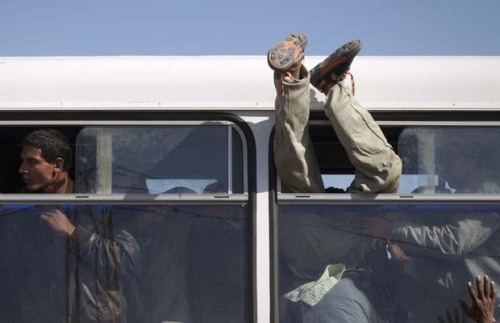 A person is helped through a bus window as Egyptian refugees who fled Libya to Tunisia leave the Echoucha refugee camp by bus on March 3, 2011 in Euchoucha. Between 8,000 and 10,000 people crossed into Tunisia on Wednesday, Adrian Edwards, spokesman from the office of the UN High Commissioner for Refugees told AFP, noting that most of those new arrivals are Bangladeshis. The UNHCR had launched an joint urgent appeal with the International Organization for Migration late Tuesday for a mass evacuation at the Tunisia-Libya border.The world in images: March 3, 2011