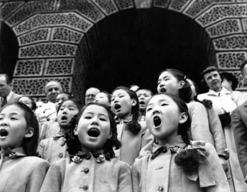 A group of young Korean children, dressed in matching outfits, sing in front of City Hall, Detroit, Michigan. 1954.