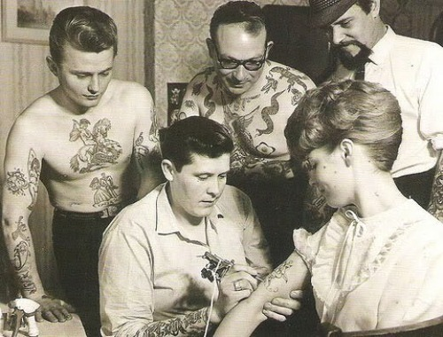 theniftyfifties:  A 1950s tattoo artist at work.  The start of the slippery slope for Amy Winehouse? And is that Eric Morecambe and Acker Bilk in the background?