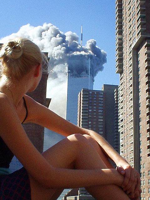 "9/11/01 ""Photo  by Ari Abramczyk.  Jaqui, 21, a fashion model and native of Austraila,  sits on the roof of her apartment in New York, NY, watching the first of  the Twin Towers burn.  The apartment she lives in is six blocks away  from the towers. She later witnesses the second plane dive into the  second tower, and both towers crashing to the ground.  (9/11/01) There  is NO PHOTOSHOP or alteration OF ANY KIND done to this image. Promise."""