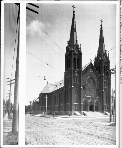 """Photograph of the exterior of St. Joseph's Catholic Church, Twelfth Street and Los Angeles Street, Los Angeles, between  1901-1915. Two tall rectangular towers with spires on top flank the main  entry of the Romanesque-style church. A large arched stained-glass  window is over the 3-arched entry. Streetcar rails and electric lines  traverse the street in front."" Church burned down 1983."