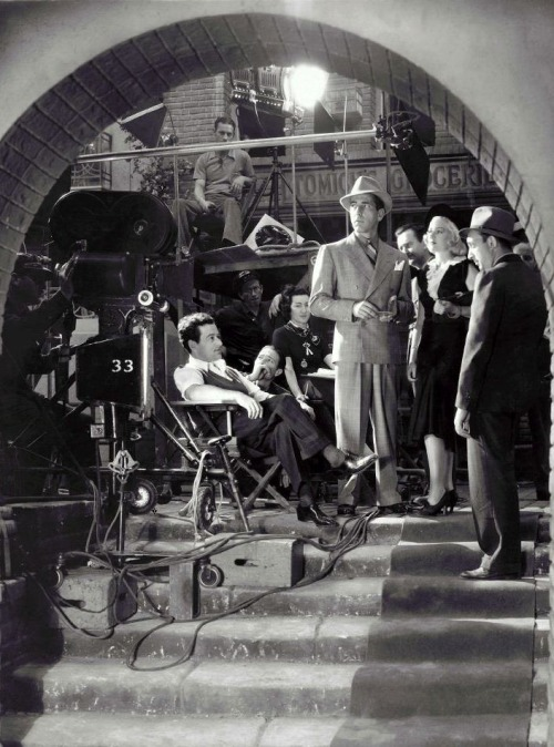 "William Wyler, Humphrey Bogart, & Claire Trevor on the set of Dead End (1937, dir. William Wyler) ""What we remember is the gangster, the man who in a sentimental moment returns to the old home. He wants to see his mother and his girl: sentiment is mixed with pride -he's travelled places; he shows his shirtsleeve - 'Look - silk, twenty bucks.' And in two memorable scenes sentimentality turns savage in him. His mother slaps his face ('just stay away and leave us alone and die'), his girl is diseased and on the streets. This is the finest performance Bogart has ever given - the ruthless sentimentalist who has melodramatized himself from the start up against the truth, and the fine flexible direction supplies a background of beetle-ridden staircases and mud and mist."" -Graham Greene, Night and Day (1937)"