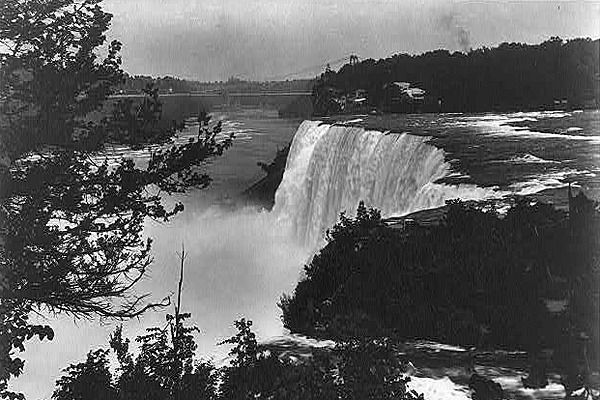 Time Travel: Niagara Falls, 1883. William Dean Howells recounts a young couple's visit to the Falls in an early issue of The Atlantic:  They drove directly to the cataract, and found themselves in the pretty  grove beside the American Fall, and in the air whose dampness was as  familiar as if they had breathed it all their childhood. It was full now  of the fragrance of some sort of wild blossom; and again they had that  old, entrancing sense of the mingled awfulness and loveliness of the  great spectacle. This sylvan perfume, the gayety of the sunshine, the  mildness of the breeze that stirred the leaves overhead, and the  bird-singing that made itself heard amid the roar of the Rapids and the  solemn incessant plunge of the cataract, moved their hearts, and made  them children with the boy and girl, who stood rapt for a moment and  then broke into joyful wonder. They could sympathize with the ardor with  which Tom longed to tempt fate at the brink of the river, and over the  tops of the parapets which have been built along the edge of the  precipice, and they equally entered into the terror with which Bella  screamed at his suicidal zeal. They joined her in restraining him; they  reduced him to a beggarly account of half a dozen stones, flung into the  Rapids at not less than ten paces from the brink; and they would not  let him toss the smallest pebble over the parapet, though he laughed to  scorn the notion that anybody should be hurt by them below.  Read more at The Atlantic's new Life channel.