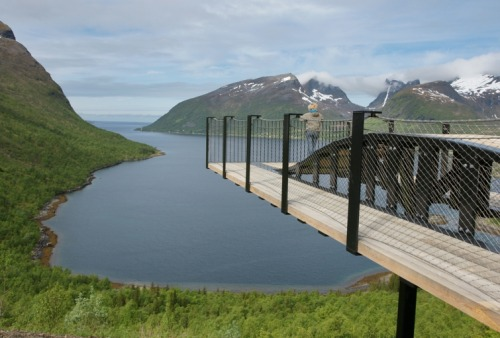 "God. Norway is cool.  The Aurland Lookout is a 98-foot-long pirate plank of a viewing  bridge that reaches out over one of the largest and most spectacular  fjords in western Norway. We're not sure what's more impressive: the  views or the fact that the only thing standing between you and the  ravine 2,133 feet below is a measly sheet of glass. The lookout was designed by the Norwegian architects Todd Saunders and Tommie Wilhelmsen,  and it's part of a more than $400 million initiative to transform  Norway's copious natural beauty into design destinations. Launched in  2002, the 18-year-long program taps predominantly young Norwegian  architects and designers to spruce up 18 designated ""National Tourist Routes""  — scenic highways — with assorted overlooks, walkways, picnic areas,  and toilets. Now, at the halfway mark, Norway has built around 120  sites, from the Aurland Lookout to an elevated concrete walkway that  winds through the trees of the Rondane National Park to a memorial for  persecuted witches (yes, persecuted witches) by Louise Bourgeois and  Pritzker Prize-winner Peter Zumthor (the only foreign architect here),  which will open this summer. All told, the federal government is expected to sink an estimated  $377 million into the program, with an additional $63 million from  private and public partners. It's a mammoth investment and a testament  to one country's faith in the power of design to add equity to an  already flourishing tourism industry.  As the initiative's rep Hege Lysholm tells Co: ""It's the nature  experience we want to emphasize. The architecture and signs and rest  areas work as an enhancement."" The structures are decided in design competitions and adhere to a  basic (and classically Scandinavian) formula: Nature first, architecture  second. Thusly, you see lots of simple designs that subtly play up the  drama of the surroundings — an undulating viewing platform that echoes  the water below, say, or a restroom whose roof follows the mountain  line. Materials like wood, glass, and concrete are selected both for  their organic aesthetic and, perhaps more importantly, because they need  to be able to withstand extreme climate, particularly in the Arctic  reaches of northern Norway.  A ton more photos when you click through."