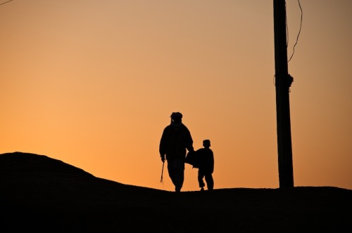 Photo of the Week Holding his son, a man walks over a hill outside Sadra Sharif, a village severely affected by the floods in Dera Ismail Khan district of Khyber Pakhtunkhwa Province, Pakistan. Many homes were destroyed in this village. The floods also damaged water sources. Through local NGOs, UNICEF is making sure flood victims are reached with safe drinking water, proper means of sanitation and health and education services. 11 March 2011© UNICEF Pakistan/2011/Shehzad Noorani