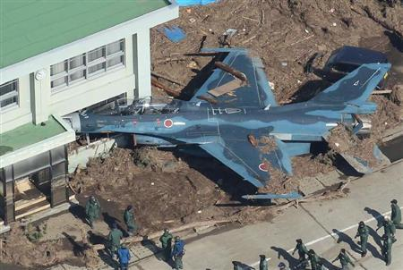 Japan's Air Force Jet F-2 was pushed and crushed into the building by Tsunami.  zenigata:  虹裏 img 流されてF-2