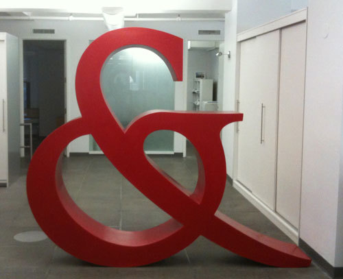 As a part of the redesign of our offices, Taylor & Ives commissioned Art Director and sculptor Dan Caspescha to build a human-size sculpture of the T&I ampersand. The 5.5″ structure was constructed from plywood and bent wood, coated with bondo, and given a bright red lacquer and clear finish. It was built with attention to detail at the Norwalk Woodworkers Club in Connecticut and took 120 hours to complete.