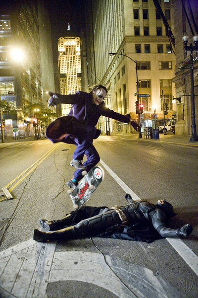 thiswarhasbeenwon: Heath Ledger as the Joker skate boarding over Christian Bale as Batman while they take a break on the set of The Dark Knight.