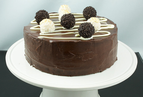 smilingfork:  Ferrero Rocher® White & Dark Cake Difficulty: ★★★★☆ (Hard) Yield: 12 Ingredients: Cake 175 g (6 ounces) butter, softened, plus extra for greasing 100 g (4 ounces) white chocolate, coarsely chopped 100 g (4 ounces) dark chocolate (70% cocoa), coarsely chopped 3 eggs 100 ml (3 1/2 ounces) whole milk 175 g (6 ounces) caster (superfine) sugar 1 teaspoon baking powder, sifted 200 g (8 ounces) self-rising flour, sifted 2 tablespoons very strong coffee 1 teaspoon vanilla extract Ganache 285 ml (9.6 ounces) heavy cream (35%) 200 g (8 ounces) dark chocolate (70% cocoa), coarsely chopped 1 tablespoon Frangelico® (optional) Decoration 50 g white chocolate, melted 5 – 6 Ferrero Garden® 5 – 6 Ferrero Rondnoir® Preparations: Cake Heat oven to 160° C (325° F).  Butter and line with non-stick baking paper, 2 X 20 cm (8 inch) round baking tins; set aside. Place the white chocolate in a heatproof bowl, set over a saucepan of just simmering water, and stir with a spatula until melted and smooth, set aside.   Repeat with the dark chocolate. In the bowl of a stand mixer fitted with the paddle attachment at medium speed, mix together the butter, eggs, milk, caster sugar, baking powder and flour and beat until creamy.  Divide the batter into two separate bowls. Add the coffee to the melted dark chocolate and stir to combine.  Add the vanilla to the white chocolate and stir to combine. Add the dark chocolate mixture to one of the bowls of batter and stir to combine.  Pour the batter into one of the prepared baking tins. Add the white chocolate mixture to the remaining bowl of batter and stir to combine.  Pour the batter into the remaining baking tin. Bake for 20 to 25 minutes or until a cake tester inserted in the centre of the cake comes out clean. Ganache Place the chocolate in a medium-sized, heatproof bowl. Bring the cream just to a boil in a small saucepan set over low-medium heat. Pour the cream over the chocolate and let stand, without stirring for 5 minutes or until the chocolate begins to melt. Using a medium-size spatula, gently stir the chocolate and cream until completely combined; begin stirring near the centre and slowly work your way toward the edge of the bowl, pulling in as much as possible, until the mixture is smooth. Add the Frangelico® (if using) and stir to combine. Let stand until cool and thickened. Decorating Using a large bread knife, slice the cooled cakes in half horizontally. Transfer one of the dark chocolate cake layers to a plate (cut side up). Using an offset spatula spread a layer of the dark chocolate ganache on top of the cake. Lay one of the white chocolate cake layers on top of the dark chocolate ganache (press down gently) and spread a layer of dark chocolate ganache. Repeat with another layer of dark chocolate cake and dark chocolate ganache. Place the final layer of white chocolate cake, cut side down (press down gently). Frost the top and sides of the cake with the remaining dark chocolate ganache. Spoon the melted white chocolate into a piping bag fitted with a fine nozzle (or use a sandwich bag and snip off the end instead).  Pipe the white chocolate in a zigzag motion over the cake. To finish the cake, garnish with Ferrero Garden® and Ferrero Rondnoir®. Slice and serve.