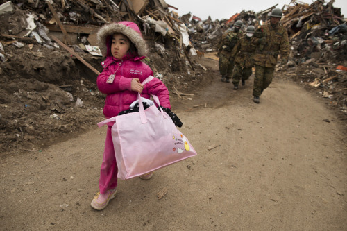Neena Sasaki, 5, carries some of the family belongings from her home that was destroyed after the devastating earthquake and tsunami on March 15 in Rikuzentakata, Miyagi province. (Paula Bronstein/Getty Images, via the Big Picture)