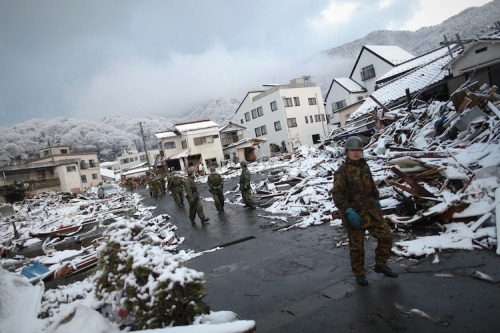 Members of the Japan Self Defense force walk through the snow-covered  ruins of Kamaishi, Iwate Prefecture, days after the area was devastated  by a magnitude 9.0 earthquake and tsunami March 16, 2011.
