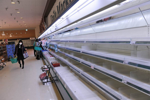 A woman walks past empty shelves at a supermarket in the northwestern city of Akita on Tuesday as panic buying sweeps the country. (via italo_pol )