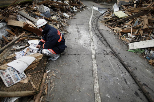 A fireman looks through pictures found in ruins of the devastated residential area of Otsuchi. Tuesday. ( via  italo_pol )