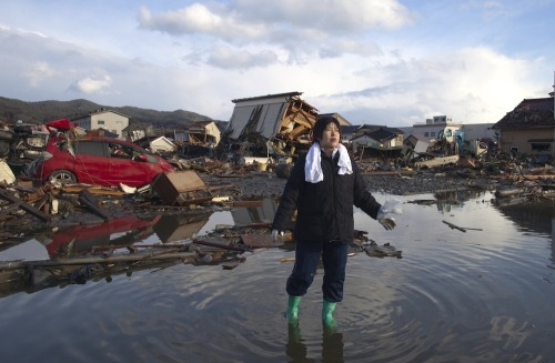 PHOTO OF THE DAY: Chieko Chiba walks through the rubble after going to see her  destroyed home on Wednesday in Kesennuma, Miyagi Prefecture, Japan. The  9.0 magnitude earthquake struck offshore on March 11, triggering a  tsunami wave of up to 10 meters which engulfed large parts of  northeastern Japan. As the death toll continues to rise, the country is  also struggling to contain a potential nuclear meltdown after a number  of nuclear reactors were seriously damaged from the quake. (Paula  Bronstein/Getty Images)