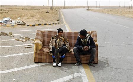 thepoliticalnotebook:  Rebel fighters sit on a sofa at a check point in Ajdabiyah, Libya.  March 15th. Photo Credit: REUTERS/Goran Tomasevic