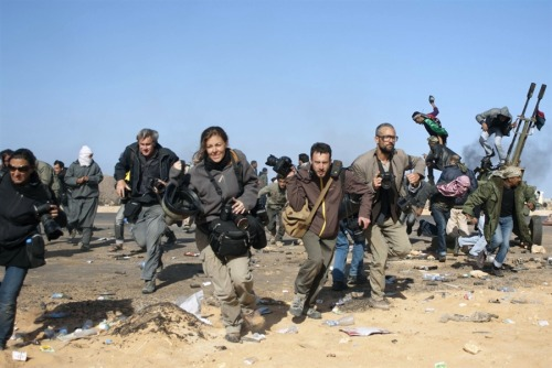 msnbc:  Journalists, including New York Times photographers Tyler Hicks (right, in glasses) and Lynsey Addario (far left), run for cover during a bombing run by Libyan government planes at a checkpoint near the oil refinery of Ras Lanuf on Friday, Mar. 11. Hicks and Addario, along with NYT correspondents Stephen Farrell and Anthony Shadid, were reported missing near lines of Muammar Gaddafi's advancing forces two days ago, the NYT announced on Wednesday. (Paul Conroy / Reuters) This is the last known photo of the NYT journalists who are missing in Libya.
