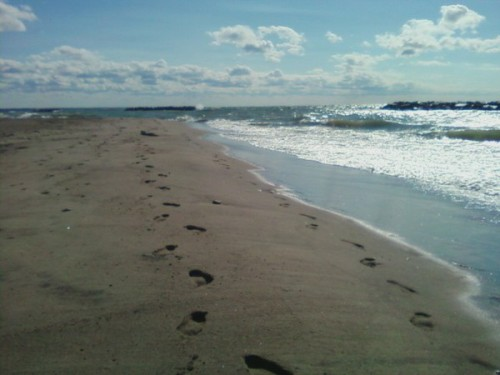 "Every time I see a picture of footprints on a sandy beach, I think of the ""Footsteps"" poem. But when I took this photo last summer at Presque Isle, it reminded me less of God; rather, it struck me with the realization of how far I've come, and how far I have yet to go. And along with the acknowledgement of what's ahead, looking back gave me the strength to move on. If I made it this far, I can certainly handle whatever is down the road. Bring it on!"