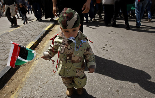 A toddler with a pacifier and military costume walks at the front a demonstration in Benghazi, Libya. | Luis Sinco/Los Angeles Times/MCTPhoto from McClatchy Newspapers.