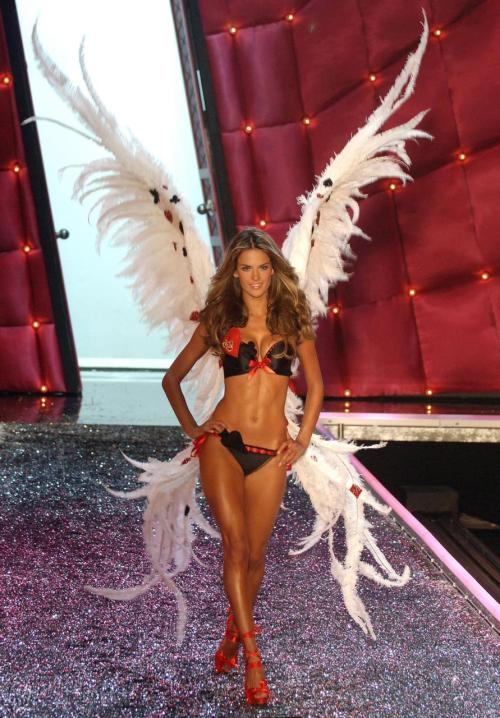 My favorite outfit from VS EVER with my favorite model EVER. Alessandra Ambrosio during the 2006 Victoria's Secret Fashion Show. Everything is perfect, one of the most beautiful women in the world in sexy black lingerie with red accents, and to top it off it's decorated with card symbols and the huge white wings that are perfect for her, just big but not overbearing and they are curved just perfectly.