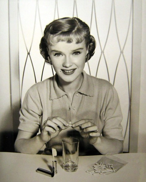 Anne Francis demonstrates a travel toothbrush and tooth powder capsules c. 1950s