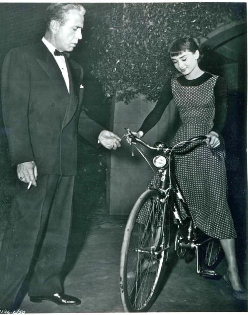 Audrey Hepburn rides a bike. Humphrey Bogart fiddles with the shifter.