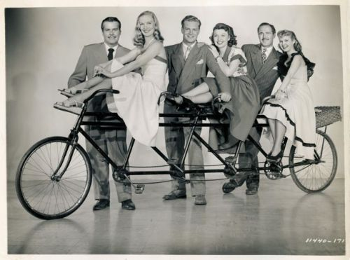 Veronica Lake, Mona Freeman and Mary Hatcher ride a bike. Billy De Wolfe, Richard Webb and Patrick Knowles stand by.