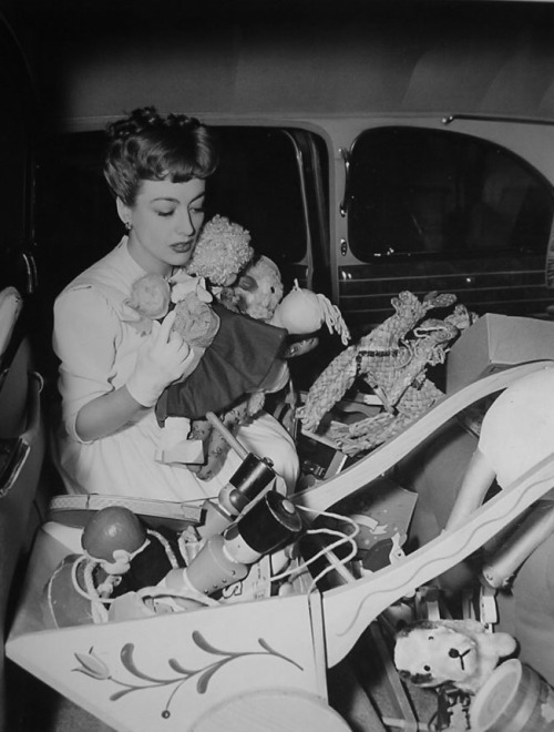 Screen star Joan Crawford, aware of the need for day nurseries to care for the children between the ages of two and six who's parents are employed in war industries, broached the idea to the American Women's Voluntary Services, was made California State Chairman of their nursery project and was the principal worker in founding the nursery in Sawtelle, a suburb of Los Angeles. Fifty children are cared for six days a week from 6 a.m. to 6 p.m. while their mothers work, many in the nearby Douglas plant in Santa Monica. Joan pays the rent, installed the furnishings, financed necessary repairs and visits the nursery regularly to help care for and entertain the children. Here she arrives early at the nursery with a carload of toys for the children.