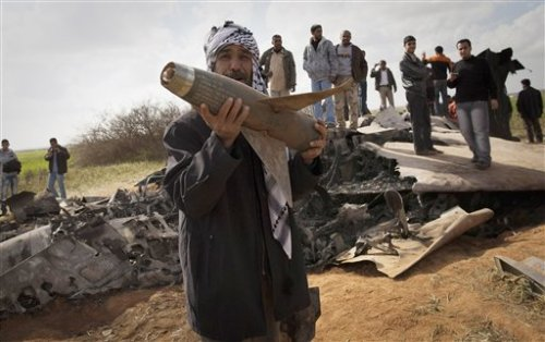 May we hope this doesn't blow up in his hands: Libyans pose with the wreckage of a US F15 fighter jet, after it crashed in an open field in the village of Bu Mariem, east of Benghazi, eastern Libya, Tuesday, March 22, 2011, with both crew ejecting safely. The U.S. Africa Command said both crew members were safe after what was believed to be a mechanical failure of the Air Force F-15. The aircraft, based out of Royal Air Force Lakenheath, England, was flying out of Italy's Aviano Air Base in support of Operation Odyssey Dawn.(AP Photo/Anja Niedringhaus)