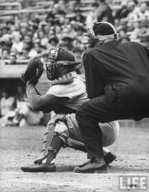 "The best sports writers have always written about baseball. mightyflynn:   … And think for a moment of the way the umpire watches the catcher as he goes about his housekeeping there behind the plate. Sometimes the arbiter has actually picked up the man's cap and mask from the ground during the play previous, and now he hands them over with an odd, uncharacteristic touch of politeness. Both of these men wear shin guards and chest protectors and masks, and although theirs is mostly an adversary relationship, they crouch in identical postures, inches apart (some umpires actually rest one hand on the catcher's back or shoulder as the pitch is delivered), and together engage in the dusty and exhausting business down behind the batter, living and scrounging on the hard corners of the sport. For one game, that is. Tomorrow, the ump working behind home will be stationed out at third base—almost a day off for him—so that he can recover from such labors, but the same catcher most likely will still be down there bent double behind the batters. Here y'are, the ump's courtly little gesture seems to say. You poor bastard.  - Roger Angell, from ""In the Fire"" - The Sporting Scene, The New Yorker, 12 March 1984 (photo: Roy Campanella & unidentified umpire, 1955, by John Dominis)"