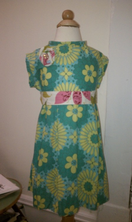 Little girl's dress I'm currently working on mass producing for boutique sales and trunk shows in April and May (with another dress as well). Dress form makes the sleeves look a little funny, but close enough.