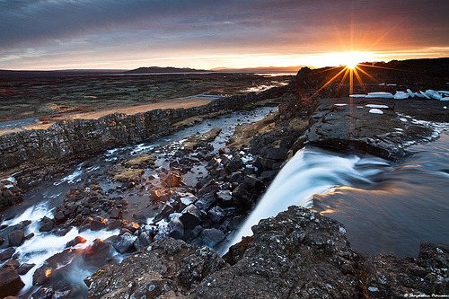Great timing on this picture. This is the Öxarárfoss (E. Axe River Fall) in the Þingvellir National Park. Legend has it and I don't know if it has been confirmed or if it is plausible, that the river was directed into the fissure. This would have brought lots of fresh water to the ancient parliament fields where Iceland's parliament was formed in the year 930. If it is true, then that made those ancient guys very good landscape artists. missjijy:  Contre Jour - Þingvellir National Park, Iceland (by skarpi)