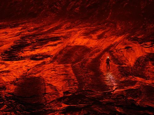"An expedition member walks on the cooled lava floor, turned red by the  reflected glow of a lake, of a caldera in Nyiragongo volcano in the  Democratic Republic of the Congo. ""Down here you feel the volcano,"" says  photographer Carsten Peter. ""It's a low-frequency rumbling that pulses  through your body—like being inside a giant subwoofer.""  via lickystickypickyme"