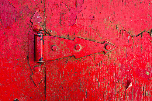 Red Hinge (by tyler.wainright) Last one from my fishing/photography trip to the Norfolk River. I spent a lot of time on the dock which had a ton of character. This hinge was on an old, weathered box that was near the fish cleaning area. I loved the combination of the red paint and the texture of the wood. Shot with a D90 with an exposure of 1/200 sec at f/4.0 with an ISO of 200. It was taken using my Nikon 35mm f/1.8 lens and edited using Adobe Camera RAW.
