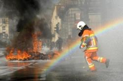 washingtonpoststyle:  Today, in one image. A firefighter runs through a rainbow during a demonstration in Brussels. More images of the day here. Photo by Geert Vanden Wijngaert (AP)