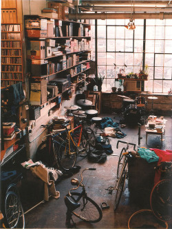Work or storage area in a converted loft apartment: bookshelves, drum kits, bicycle parts.