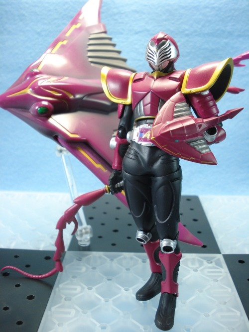KAMEN RIDER RAIA aka Miyuki Tezuka (played by  Hassei Takano)Quick Info: A mysterious and enigmatic fortune-teller who believes in predestination, Tezuka was not personally picked  to receive a Card Deck. The original deck holder was his friend Yuichi Saito who refused to participate in the Rider War and was killed. Tezuka takes the Advent Deck on his behalf and becomes Kamen Rider Raia to avenge his friend by ending the Rider War himself. A melee-based fighter, he uses his Swing Vent to summon a whip and the Evil Visor mounted on his left forearm as a small shield. Alternately, he can use his Copy Vent to duplicate an opponent's weapon. His Final Vent, Hide Venom allows him to ride on Evildiver's back and ram into an opponent.EVILDIVER is modeled after a sting-ray and was originally the contract Monster of Kamen Rider Raia. It later came into the possession of Kamen Rider Ouja when it tried to avenge its master in vain. Together with Venosnaker and Metalgelas, Evildiver became one of the building blocks of the composite Monster Genocider.