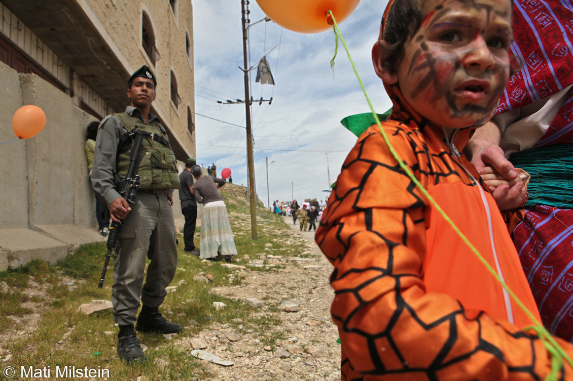 Purim in Hebron IIIJewish settlers celebrate the Purim holiday under heavy Israeli  military guard on 20 March in the divided West Bank city of Hebron. In this photo, a costumed child walks past an Israeli Border Police officer.