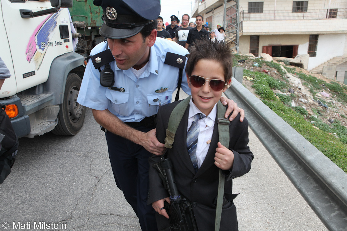 Purim in Hebron V: Guns! Not just for adults!Jewish settlers celebrate the Purim holiday under heavy Israeli  military guard on 20 March in the divided West Bank city of Hebron. In this photo, Hebron's Israeli police commander moves to confiscate a toy assault rifle from a Jewish boy in costume.