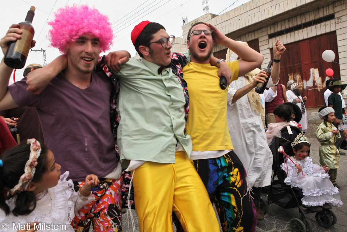 Purim in Hebron VII: The True North Strong and FreeJewish settlers celebrate the Purim holiday under heavy Israeli  military guard on 20 March in the divided West Bank city of Hebron. In this photo, Canadian Jews drink as they march along with local settlers.