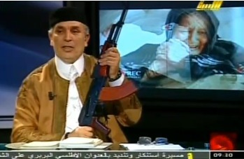 "nightline:  Not a format we've tried yet: Libyan newsreader brandishes rifle on television Last week's video. BBC: A presenter on a pro-Gaddafi television station in Libya has pledged to fight until his ""last drop of blood, last baby and child"" during an on-air tirade. The newsreader brandished an automatic weapon on Al Libya and branded the opposition traitors.  Two things: You really should do it, just once, and until I read your caption I thought I was looking at a still from SNL's Weekend Edition. — Michael"
