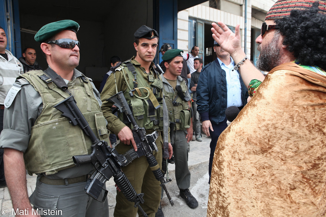 Purim in Hebron VIII: Gaddafi in HebronJewish settlers celebrate the Purim holiday under heavy Israeli  military guard on 20 March in the divided West Bank city of Hebron. In this photo, Israeli security personnel block a Jewish settler dressed as Libyan leader Muammar Gaddafi from approaching a Palestinian storefront.