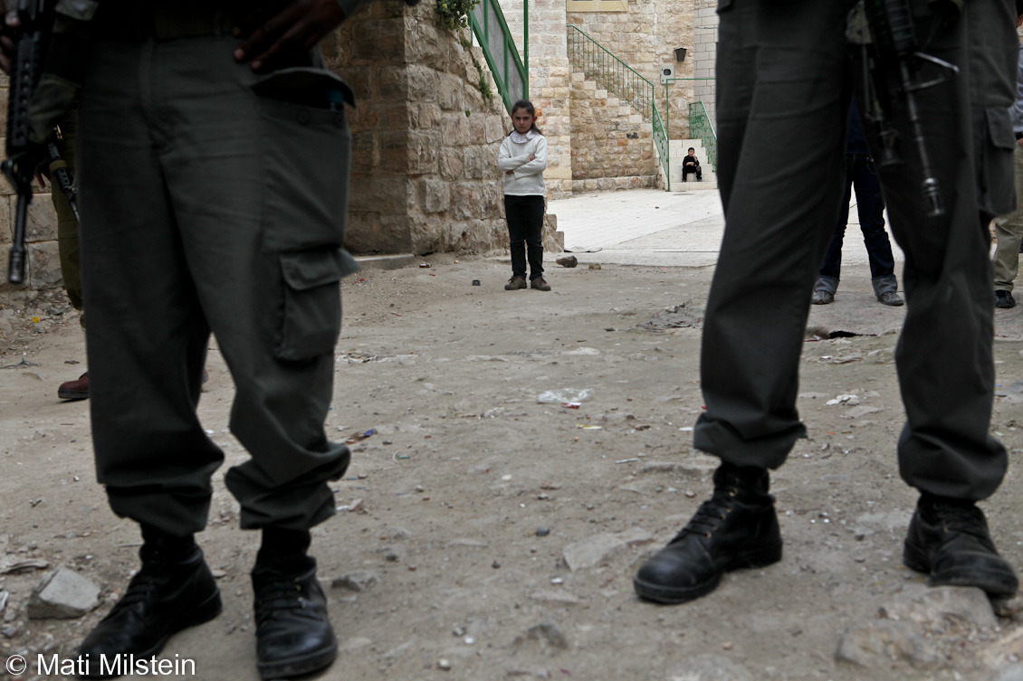 Purim in Hebron XII: Between the LinesJewish settlers celebrate the Purim holiday under heavy Israeli  military guard on 20 March in the divided West Bank city of Hebron. In this photo, a Palestinian girl stands behind Israeli troops as the holiday procession passes her house. The image also appears in the British Embassy-Israel's latest quarterly human rights report on Israel & the Palestinian Territories.